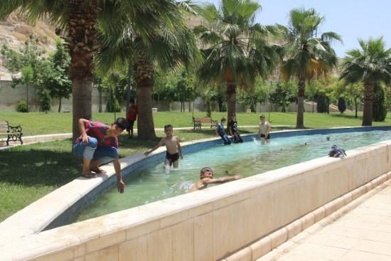 Çocuklar süs havuzlarında serinliyor