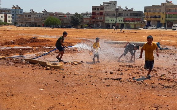 Sıcaktan bunalan çocuklar çamurda halay çekip hortumla serinledi (Video)